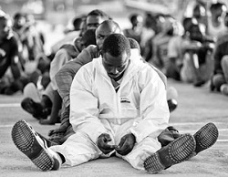 Migrants rest after disembarking in the Sicilian harbour of Augusta